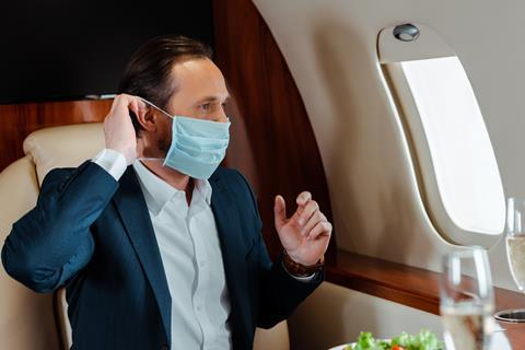 Business jet traveller with mask credit Shutterstock